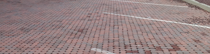 Red brick road with parking spots